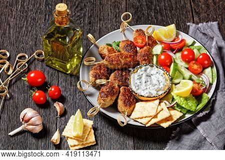 Spicy Lamb And Feta Kofta Skewers With Fresh Tomatoes, Mint, Red Onion Slices, Crackers, And Tzatzik