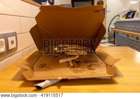 Leftover Pieces Of Pizza Crust Laying In The Pizza Box Carton. Leftovers Pizza In A Cafe