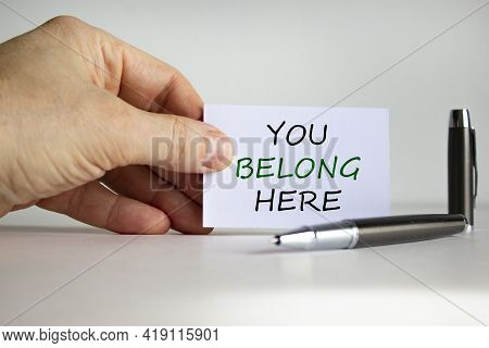 You Belong Here Symbol. White Paper With Words 'you Belong Here' In Businessman Hand, Metalic Pen. B