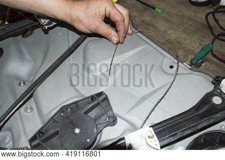 The Torn Cable Of The Car Window Lifter Drive In The Hands Of A Mechanic