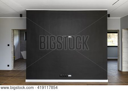 Black Mat Tv Wall In The Living Room With Electrical, Antenna And Tv Connectors And A Conduit For Ca