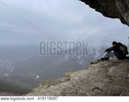 Guamka, Russia April 17, 2021: Tourists On Huge Cliff With Spectacular View Of Nature. Group Of Peop