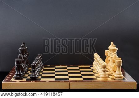 Wooden Chess. Chess Pieces Are Located On A Chessboard On A Black Background. Closeup. Full Depth Of