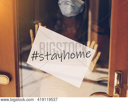Coronavirus Covid-19 Quarantine. Desperate Scared Woman With Face Mask In The Window. Stay At Home A