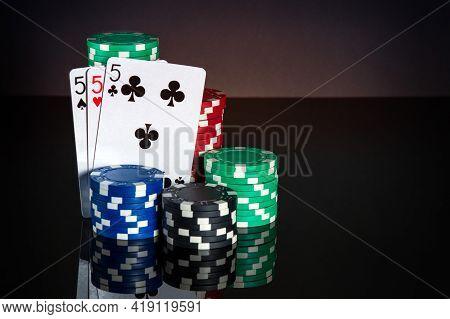 Poker Cards With Three Kind Or Set Combination. Close-up Of Playing Cards And Chips In Poker Club. F