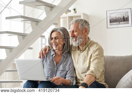 Happy Older Mid Age Family Couple Using Laptop Sit On Couch. Smiling Senior Adult Mature Man And Wom