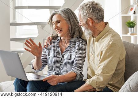 Happy Middle Aged Mature Couple Waving Greeting Family Having Virtual Meeting Using Laptop Computer