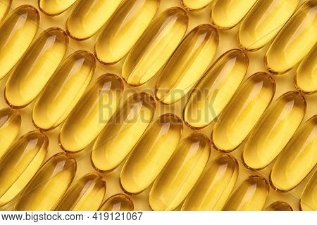 Fish Oil Capsules In A Row, Omega 3 Softgels On Yellow Geometric Background.