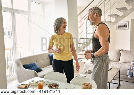 Happy Healthy Fit Mature Family Couple Drinking Juice And Laughing At Home. Smiling Sporty Senior Ad