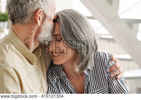 Happy Affectionate Mature Adult Husband Embracing Kissing Wife Enjoying Tender Moment Or Love And Ca