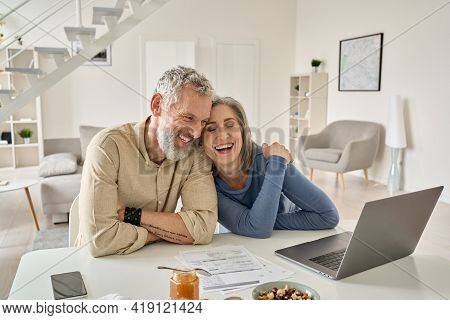 Happy Mature Older Family Couple Laughing, Bonding Sitting At Home Table With Laptop. Smiling Middle