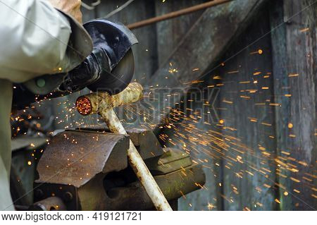 Pipe Cutting With A Circular Grinder. A Man's Hand, Cuts Pieces Of Pipe With A Grinder. Power Tool,