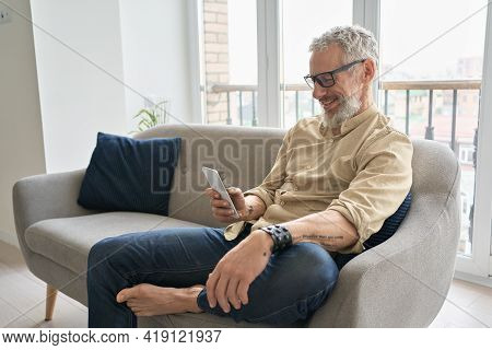 Happy Older Middle Aged Man Using Apps On Phone Relaxing Sitting On Couch At Home. Smiling Senior Hi