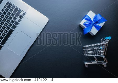 Web Shopping. Laptop Computer, Shopping Trolley And White Gift With Blue Ribbon On Dark Background.