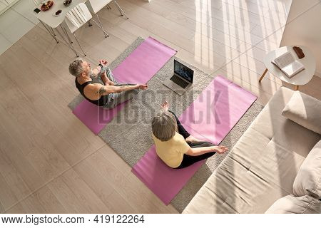 Fit Senior Old Couple Doing Virtual Yoga Class Breathing Exercises Together At Home, Top View. Matur