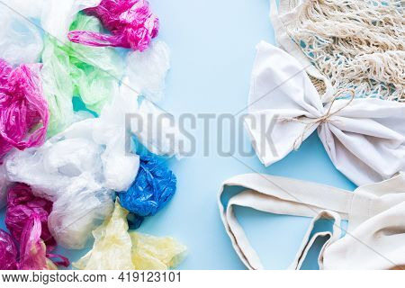 Many Disposable Plastic Bags Vs Reusable Cotton Bags On A Blue Background. Zero Waste Shopping. Sust