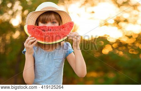 Shy Little Girl In Hat Hold Big Slice Of Watermelon And Hide Her Face Outdoor. Summer Holidays Full