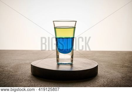 Homemade Yellow And Blue Transparent Alcohol Drink In Glass Of Limoncello And Curacao, Close Up Conc