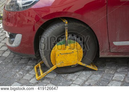A Front Car Wheel Blocked By Wheel Lock For Unauthorised Or Illegal Parking. A Wheel Clamp Also Know