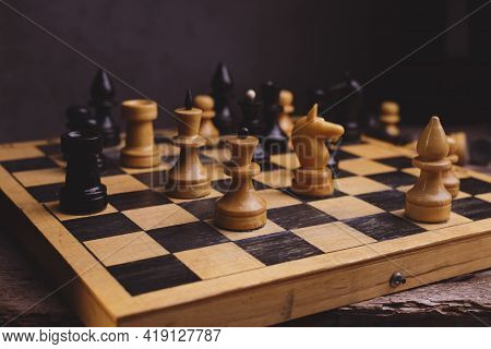 Wooden Chess Pieces On The Old Chessboard Against Dark Background.