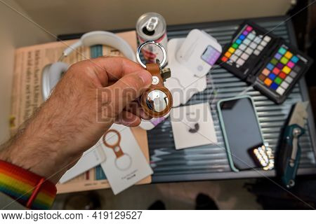 Paris, France - May 2, 2021: Man Presenting After Unboxing New Airtag - Small Device Helps People Ke