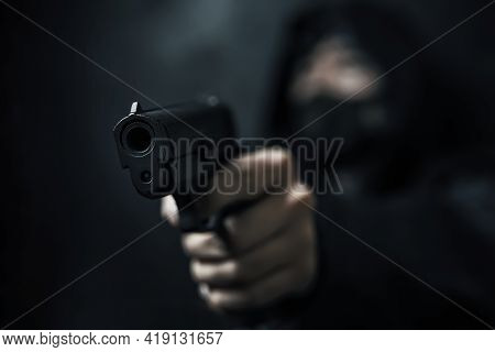Masked Robber With Gun Aiming Into Camera. Man In Hood Threatens With Firearm. Weapon In Persons Han