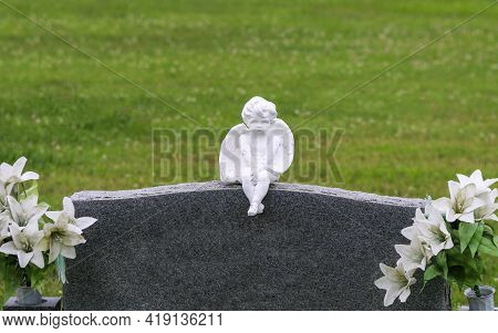 Cherub Statue Carving On Unmarked Graveyard Cemetery Headstone Marker With With Flowers