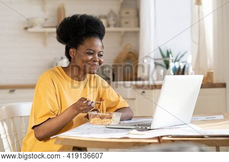 African Girl Eat And Watch Funny Video, Film On Laptop, Webinar For Study Or Make Conference Call To