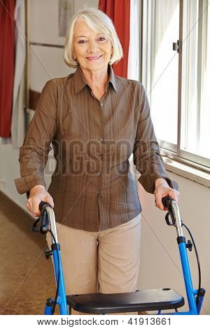 Senior woman walking with walker through a rest home