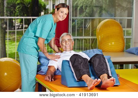 Senior man getting rehab at physiotherapy in nursing home