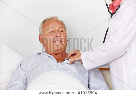 Senior man in hospital bed getting auscultating with stethoscope from a nurse