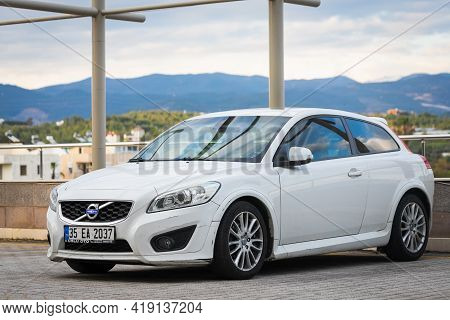 Alanya, Turkey - April 15 2021: White Volvo C30 Parked On The Street On A Warm Summer Day Against Th