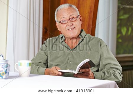 Senior man reading a book with reading glasses in a rest home