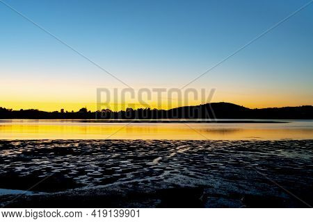 Silhouettes And Wet Sand Patterns At Low Tide In Morning Sunrise Light Across Tautaunga Harbour.