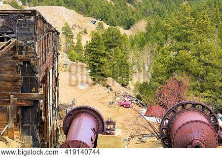 Abandoned Wooden Mining Mill Surrounding Industrial Equipment And An Alpine Pine Forest Taken In The