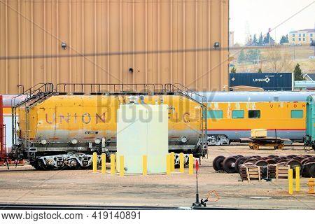April 26, 2021 In Cheyenne, Wy:  Union Pacific Rail Yard Including A Vintage Passeneger Rail Car Bey