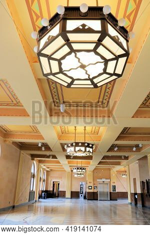 April 26, 2021 In Cheyenne, Wy:  Vintage Lighting Fixture On The Decorative Ceiling Of The Lobby At