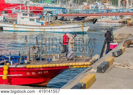 Daecheon, South Korea; April 25, 2021: Unidentified People Carrying Fishing Tackle Disembark From Tr