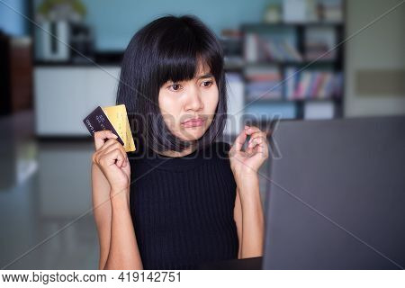 Strain Woman. Girl Holding Credit Card And Use Computer Laptop. She Have An Expression Of Concern An