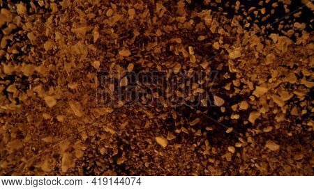 Instant coffee grains explosion, top view. Isolated on black background