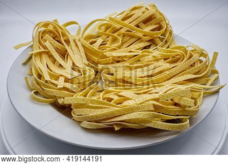 Fresh Raw Italian Tagliatelle In A White Dish Isolated On White Background