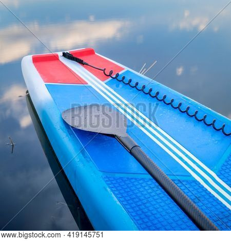 Deck of a racing stand up paddleboard with a paddle and safety leash.