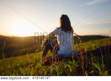 Woman in nature in sunset. People in nature. Blurred image of woman relaxing in nature in sunset. people. Happy people. Happy beautiful woman in nature in sunset. Woman sitting in meadow in sunset. Woman. People. Sunset. Nature.