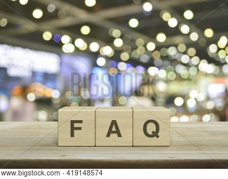Faq Letter On Block Cubes On Wooden Table Over Blur Light And Shadow Of Shopping Mall, Frequently As
