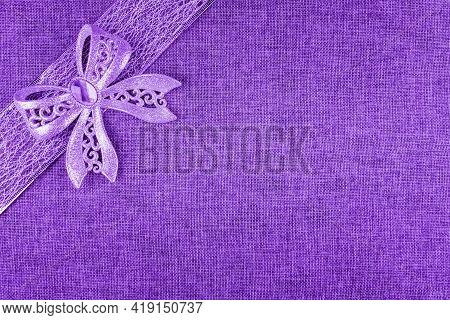 Elegant Shiny Purple Glitter Bow On Purple Colored Ribbon And On Bright Purple Burlap. Horizontal Gr