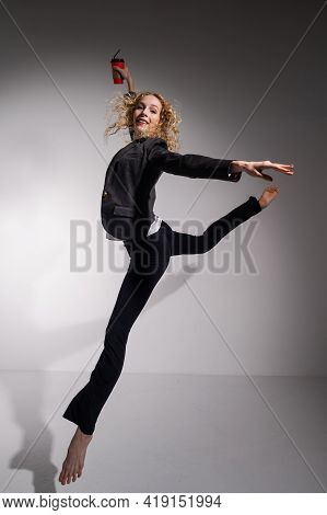 Graceful Barefoot Ballerina In A Business Suit Jumping With A Glass Of Coffee In Her Hands On A Whit