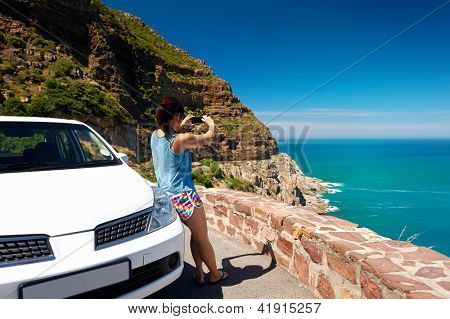 Tourist woman taking a photograph of scenic ocean mountain road chapmans peak in cape town south africa with rental car poster