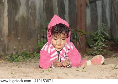 Close-up Portrait Of An Asian Little Baby Boy Child Playing On Sandy Ground. Concept To Childhood, B