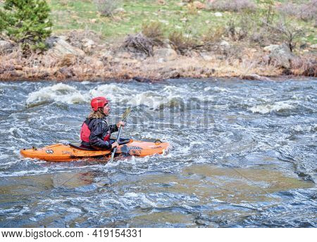 Fort Collins, CO, USA - April 30, 2021: Young male kayaker is running rapids on the Poudre River in early spring, beginning of the paddling season.