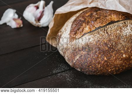 Close-up Of Crusty Sourdough Round Bread Made Of Whole Grain In Craft Package With Garlic. Natural A